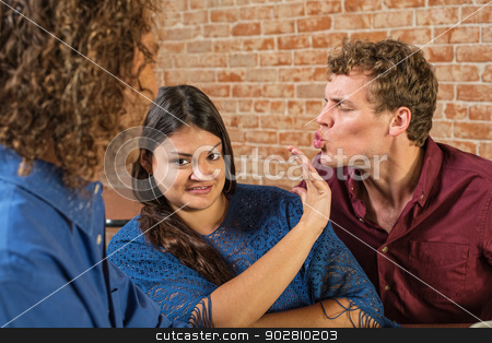 Man Kissing Annoyed Woman stock photo, Annoyed woman being kissed by European male by Scott Griessel