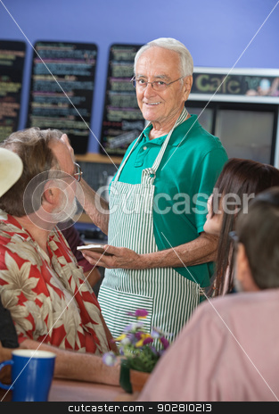 Smiling Cafe Worker with Customers stock photo, Older cafe worker with patrons in restaurant by Scott Griessel