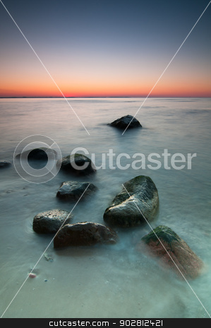 Seascape Sunset stock photo, Sunset scenic view over Baltic Sea with stones in foreground. Long exposure. by Tiramisu Studio