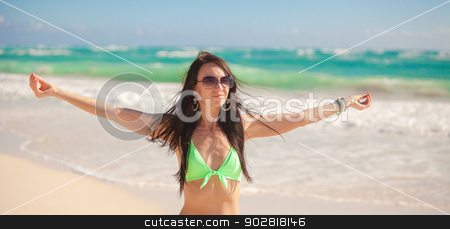 Young woman enjoying the holiday spread her hands on a white, tropical beach stock photo, Young beautiful woman enjoying the holiday spread her hands on a white, tropical beach by Dmitry Travnikov