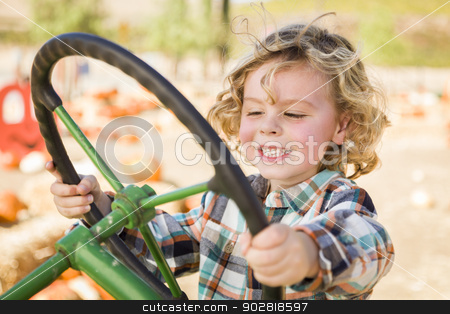 Adorable Young Boy Playing on an Old Tractor Outside stock photo, Adorable Young Boy Playing on an Old Tractor in a Rustic Outdoor Fall Setting.  by Andy Dean