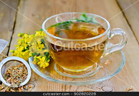 Herbal tea from tutsan in strainer with cup stock photo, Tea in a glass cup, a metal filter for tea with dried flowers tutsan, Hypericum fresh flowers on the background of wooden boards by rezkrr