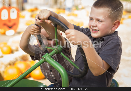 Adorable Young Boys Playing on an Old Tractor Outside stock photo, Adorable Young Boys Playing on an Old Tractor in a Rustic Outdoor Fall Setting.  by Andy Dean