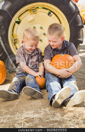 Two Boys Holding Pumpkins Talking and Sitting Against Tractor Ti stock photo, Two Boys Sitting Against a Tractor Tire Holding Pumpkins and Talking in Rustic Setting. by Andy Dean
