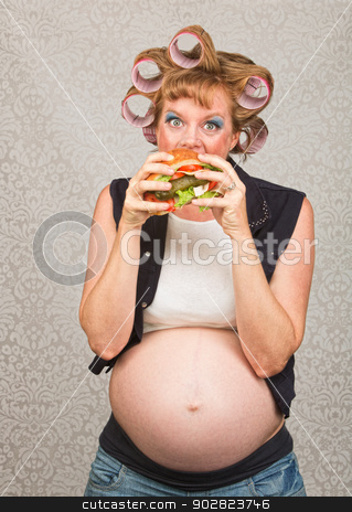 Hungry Pregant Woman Eating stock photo, Young pregnant single female eating a sandwich by Scott Griessel