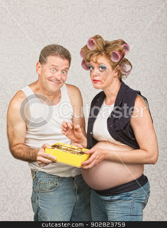 Smiling Man Feeding Pregnant Woman stock photo, Guilty pregnant woman eating candy with smiling man by Scott Griessel