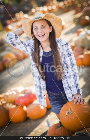 Preteen Girl Playing with a Wheelbarrow at the Pumpkin Patch stock photo, Preteen Girl Wearing Cowboy Hat Playing with a Wheelbarrow at the Pumpkin Patch in a Rustic Country Setting.  by Andy Dean