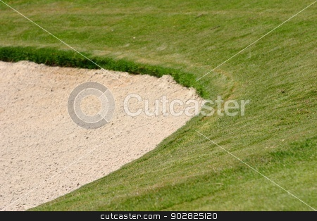 Golf Bunker stock photo, Green grass surrounding a golf bunker. by Henrik Lehnerer