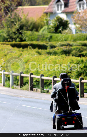 Mobilty scooter and senior man stock photo, Rear view or senior man riding mobility scooter on countryside road. by Martin Crowdy