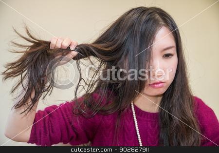 Frustrated woman stock photo, Young woman pulling her hair looking frustrated by Yanming Zhang