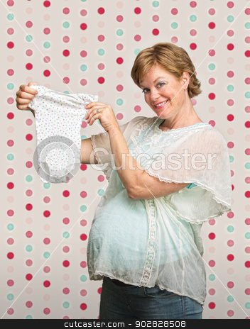 Expecting Mother with Baby Clothes stock photo, Proud young pregnant woman showing off baby clothes by Scott Griessel