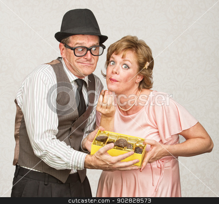 Husband Holding Candy for Pregnant Woman stock photo, Awkward man holding box of chocolate for pregnant woman by Scott Griessel