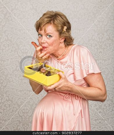 Pregnant Lady Tasting Chocolates stock photo, Happy expecting woman holding chocolates and licking fingers by Scott Griessel