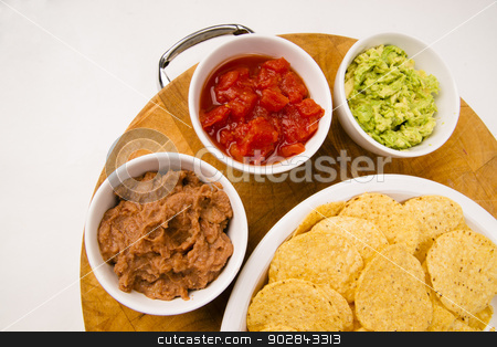 Chips Salsa Refried Beans Guacamole Nachos Food Fresh Appetizer stock photo, Food Appetizers Chips and Salsa Refried Beans Guacamole on Wood Cutting Board by Christopher Boswell