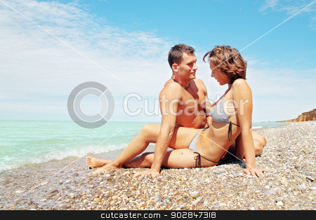 on the beach stock photo, Young beautiful pair rests on the beach by Iuliia   Malivanchuk
