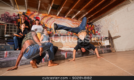 Capoeira Performers Flipping stock photo, Group of capoeira performers in urban building doing flips by Scott Griessel