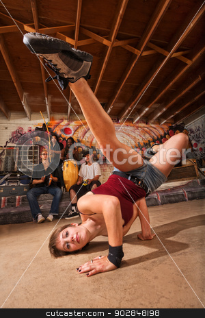 Female Capoeira Performer Kicking stock photo, Young female capoeira performer kicking from the ground by Scott Griessel