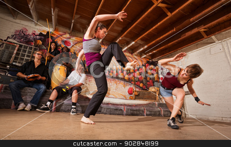 Female Capoeira Performers Sparring stock photo, Two female capoeira performers sparring indoors while music plays by Scott Griessel