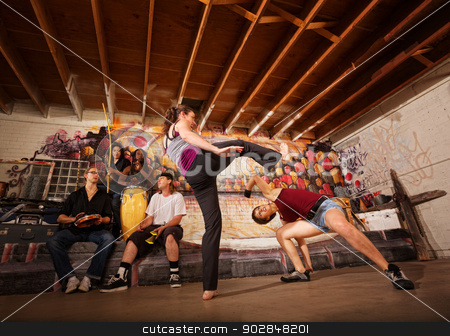 Woman Dodging a Front Kick stock photo, Woman dodging a capoeira front kick indoors by Scott Griessel