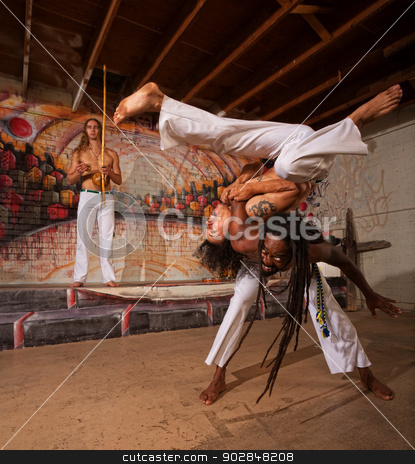 Capoeira Performers Shoulder Throw stock photo, Capoeira man throwing partner over his shoulders by Scott Griessel