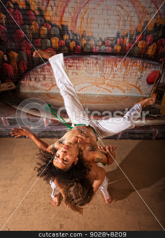 Capoeira Performers Doing Throws stock photo, Capoeira performers practicing back shoulder throwing indoors by Scott Griessel