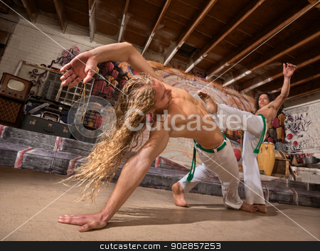 Male Capoeira Performers stock photo, Young male capoeira partners performing kicks indoors by Scott Griessel