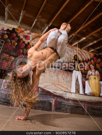 Agile Capoeira Expert stock photo, Agile capoeira performer with musicians in urban building by Scott Griessel