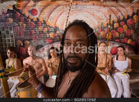 Handsome Capoeira Master with Instruments stock photo, Handsome African capoeira master with students playing music by Scott Griessel