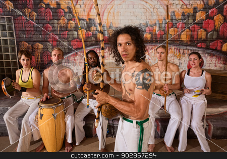 Latino Capoeira Performer with Group stock photo, Handsome Latino Capoeira expert with musical instruments by Scott Griessel