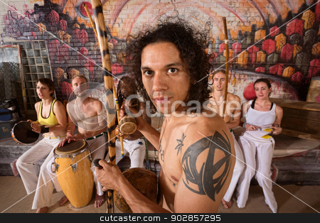 Capoeira Performers Playing Music stock photo, Handsome Latino capoeira expert with tattoo and musical instrument by Scott Griessel