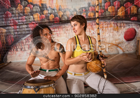 Capoeira Couple Playing Traditional Instruments stock photo, Cute young couple in capoeira outfit playing traditional instruments by Scott Griessel