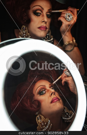 Woman Applying Eye Shadow stock photo, Drag queen applying makeup in front of a mirror by Scott Griessel