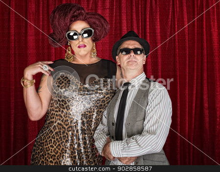 1960s Retro Drag Queen with Man stock photo, Tall drag queen and retro style man in sunglasses by Scott Griessel