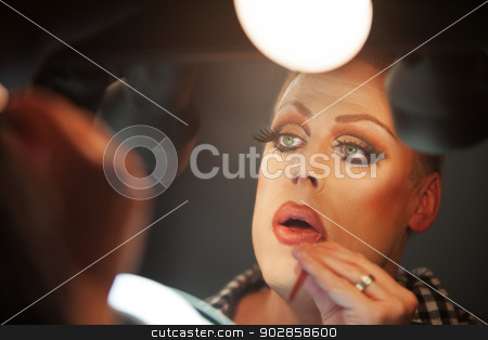 Close Up of Man with Makeup stock photo, Close up of serious man preparing makeup on face by Scott Griessel