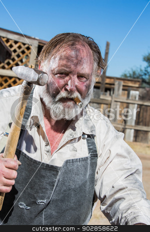 Old West Blacksmith stock photo, Old West Blacksmith Holds Hammer While Smoking a Cigar by Scott Griessel