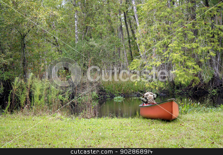 Canoe on a Creek Bank stock photo, A canoe containing a camouflage tactical backpack with dual canteens rests on the bank of a creek in a lush, tropical forest. by Carl Stewart