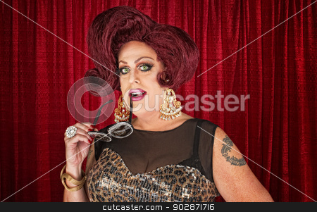 Man in Drag Biting Sunglasses stock photo, Grinning drag queen biting sunglasses in theater by Scott Griessel