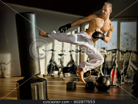 Shirtless young man doing flying kick stock photo, Shirtless handsome muscular young man in gym doing flying kick, wearing boxing gloves by Stefano Cavoretto