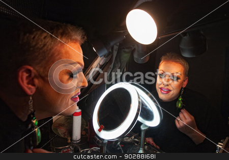 Drag Queen in Makeup Room stock photo, Caucasian drag queen at mirror in dressing room by Scott Griessel