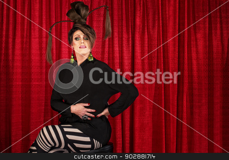 Serious Seated Man in Drag stock photo, Serious man in drag seated in front of curtain by Scott Griessel
