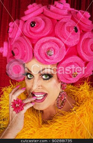 Grinning Drag Queen Biting Fingernails stock photo, Grinning drag queen in plastic wig biting fingernails by Scott Griessel