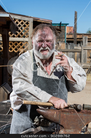 Old West Blacksmith stock photo, Old West Blacksmith Smokes Cigar While Resting Hammer on Anvil by Scott Griessel
