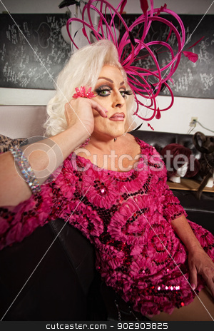 Blond Drag Queen Sitting stock photo, Blond drag queen in pink dress sitting on sofa by Scott Griessel