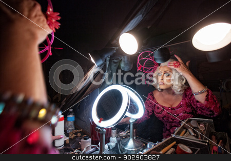Man Fixing Hair in Mirror stock photo, Female impersonator adjusting hair in dressing room by Scott Griessel