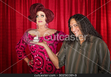Man Giving Bored Woman Dessert stock photo, Grinning man holding muffin for indifferent woman in pink by Scott Griessel