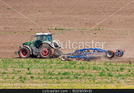 Tractor working on the field stock photo, Tractor plowing field with harrow, a detail side view by Marian Bauer