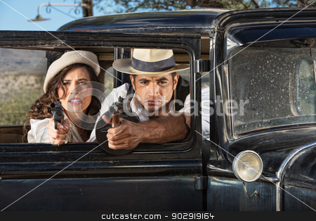 1920s Male and Female Gangsters stock photo, 1920s vintage gangsters firing guns from car window by Scott Griessel