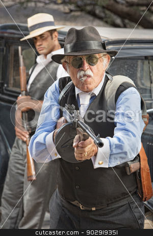 Middle Aged Gangster Aiming stock photo, 1920s vintage gangsters outside holding weapons next to car by Scott Griessel