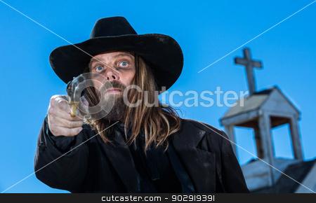Serious Cowboy With Gun stock photo, A serious cowboy holding a gun near a church by Scott Griessel
