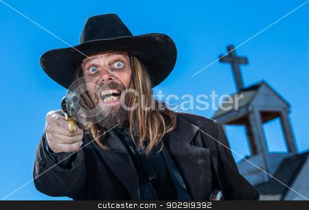 Laughing Cowboy With Gun stock photo, A laughing cowboy holding a gun near a church by Scott Griessel